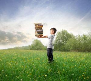 Niño sosteniendo libros en un campo verde